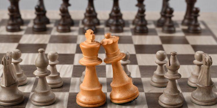 Imagem de um tabuleiro de xadrez com as peças do Rei e da Rainha com cor destacada