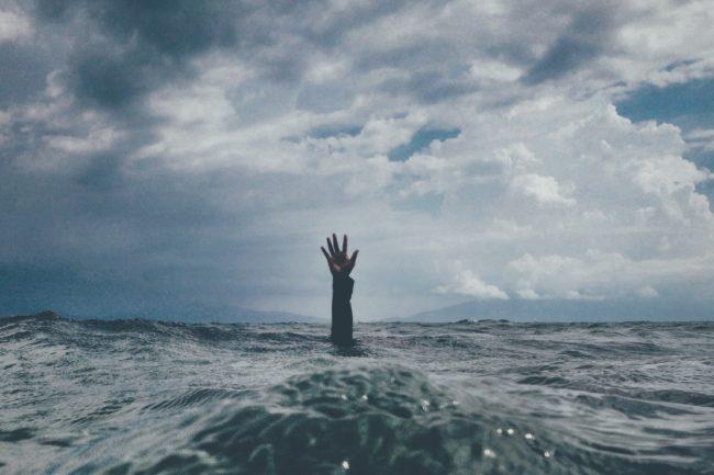 Braço fora da água com céu ao fundo