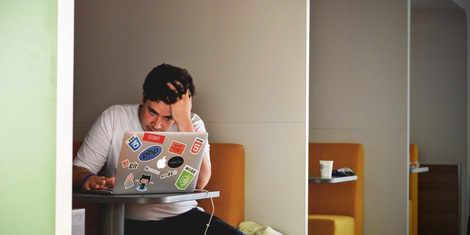 Rapaz diante de notebook com testa franzida e olhar de frustração enquanto passa as mãos pelos cabelos