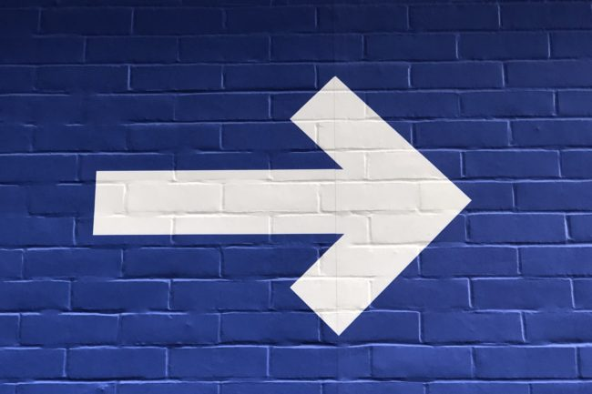 Desenho de seta branca apontada para o lado direito em parede de tijolos azuis