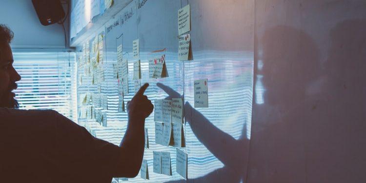 Pessoa (utilizando a metodologia ágil) apontando para post-it em quadro branco