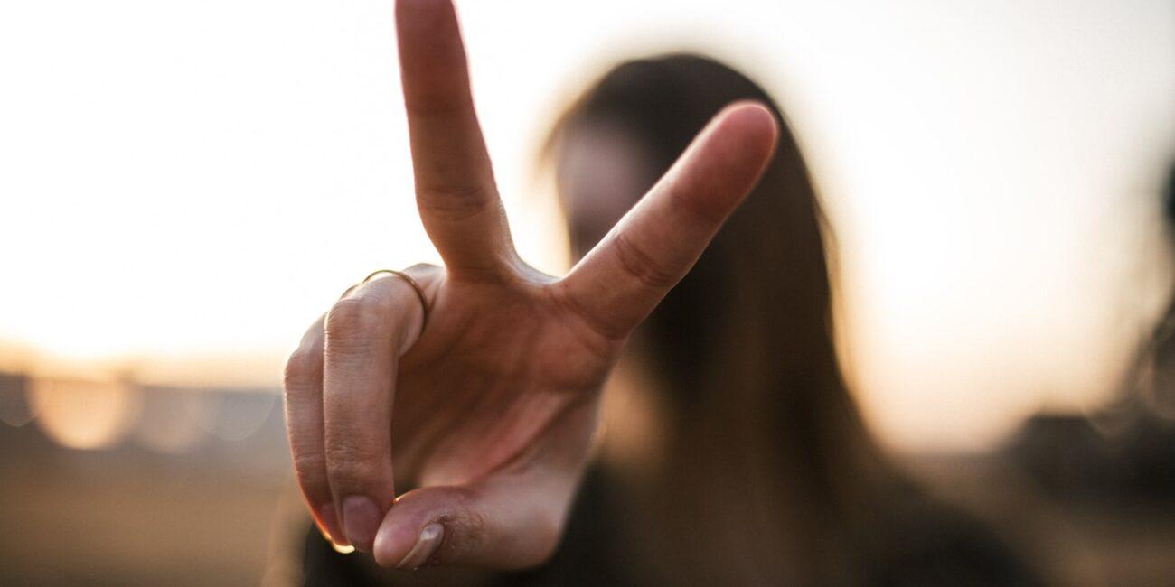 Uma mulher fazendo o sinal de paz e amor com as mãos