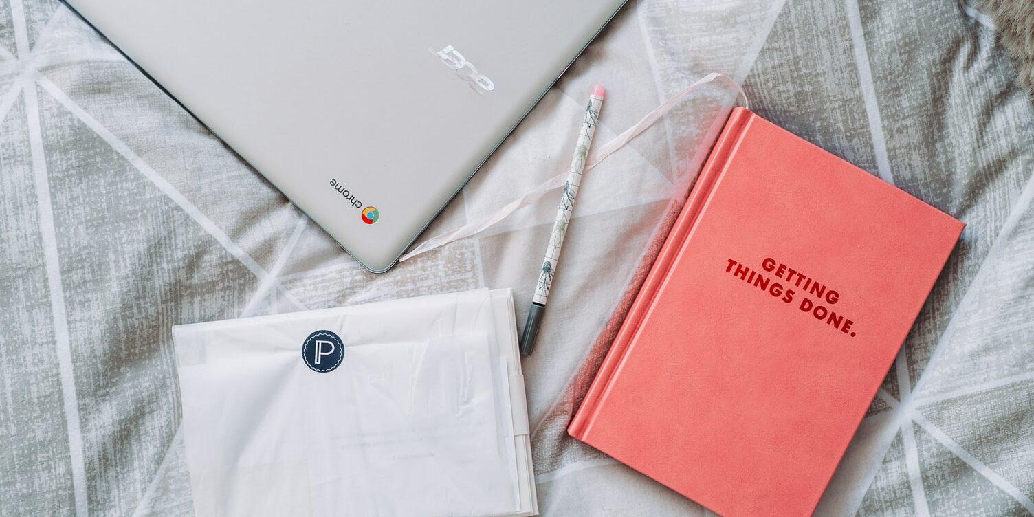 notebook, caneta e um livro com a frase: getting things done